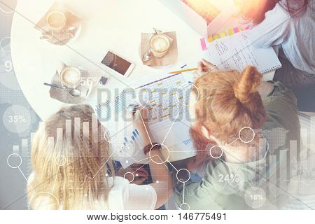 Visual effects. Overhead shot of team of young partners discussing business ptoject analyzing financial data making notes in graphics and diagrams sitting at table with copy space mobile on it