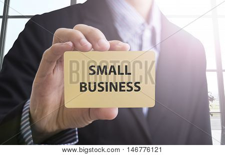 businessman hand holding a business card with a message small business for advertise concept.