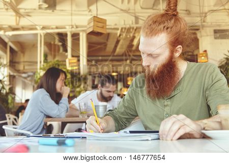 Portrait Of Young Caucasian Journalist With Long Beard Holding Pencil, Writing Down In His Notebook,