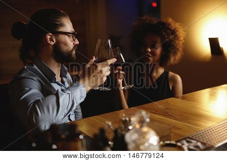 Fashionable Interracial Couple Drinking Wine During Date, Sitting At Restaurant, Having Romantic Eve