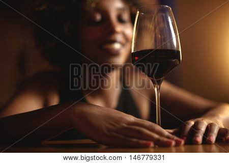 Cropped Shot Of Dark Skinned Female Touching Glass Of Red Wine With Both Hands, Selective Focus On D
