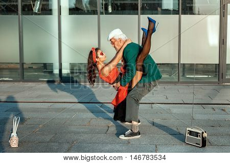 Old man dancing with a young girl in retro style.