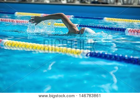 Strong female swimmer in the motion in the swimming pool outdoors. She wears a swimsuit, a white swim cap and swim glasses. Horizontal.
