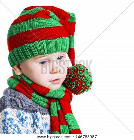 Christmas Boy In Knitted Cloths Looks Down Sad