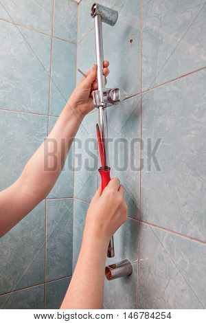 Replace broken wall mounted vertical height adjustable shower bar slider rail holder close-up of hands remove the faulty slide rail.