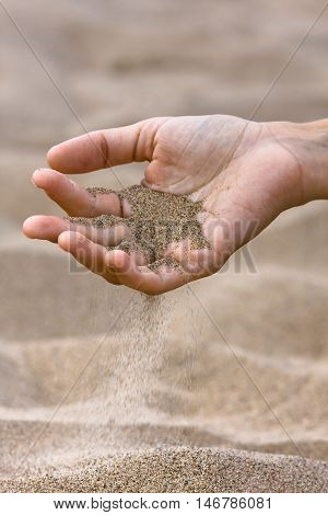 sand running through hand on the beach background