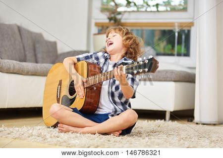 Happy boy singing and playing the guitar at home