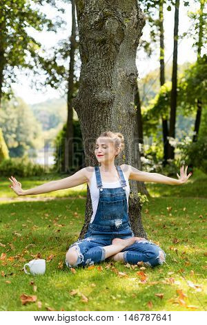 Young Blonde Woman Drinking Coffee Or Tea In The Forest Sitting In Lotus Pose And Enjoying The Warm
