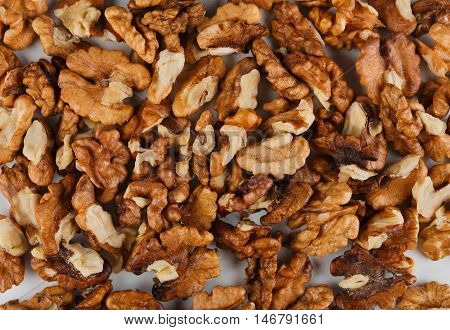 Pile of peeled skinless walnuts close-up as abstract food background. Lots of peeled brown hazel nut seeds, healthy vegan and vegetarian food, rich of energy low fat nutrition