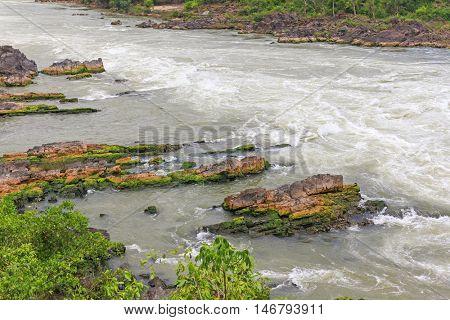 Rapid water flowing from Khone Pha Pheng (Khon Pha Pheng) waterfall, known as Niagara of the Asia, along stone riverbank in Champasak, Southern Laos