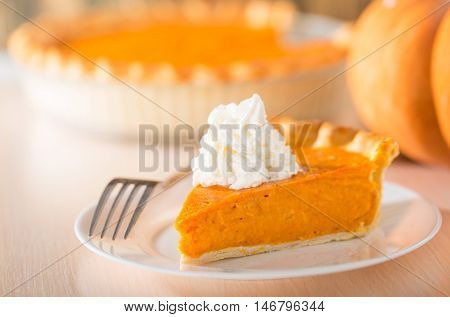 Pumpkin pie with swirls of whipped cream on decorative plate.  Whole pie in soft focus in background.  Macro with shallow dof