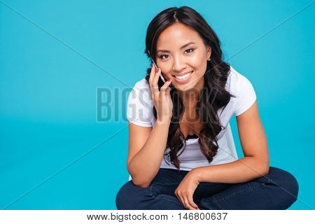 Portrait of a cheerful smiling asian woman talking on the phone while sitting on the floor isolated on a blue background