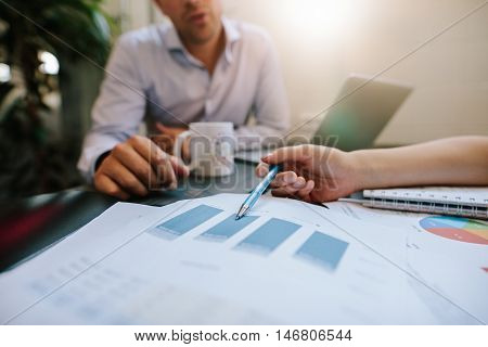 Business People Discussing Financial Statistics In Office