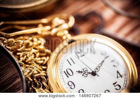 Vintage compass, binoculars, pocket watches on sand background