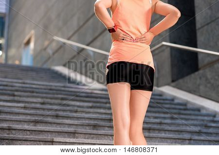 Back view of young woman in sportswear touching her lower back muscles by painful injury standing on the stairs.