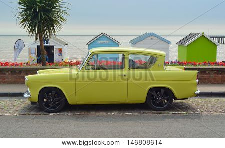 Felixstowe, Suffolk, England - August 27, 2016: Classic Yellow Ford Anglia motor car on seafront road in front of beach huts.