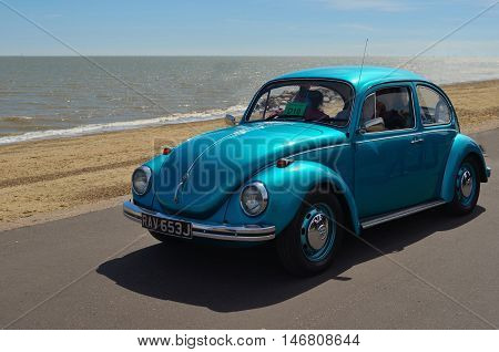 Felixstowe, Suffolk, England - May 01, 2016: Classic Blue  Volkswagen Beetle being driven along Felixstowe seafront promenade.