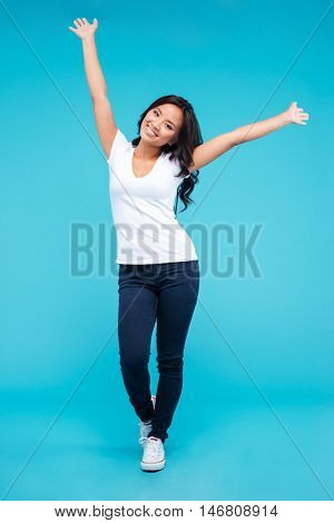 Cheerful young asian woman standing with raised up hands isolated on a blue background