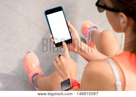 Sports woman holding a smart phone with empty screen to copy paste. Mobile phone program for sport