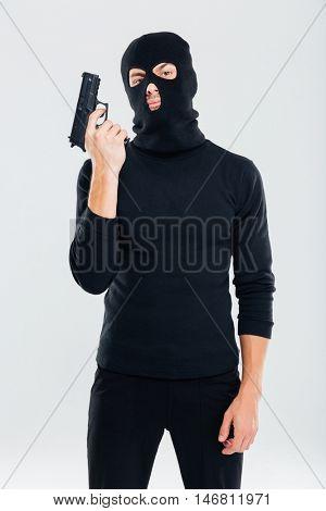 Criminal man in balaclava standing and holding gun