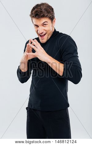 Sneaky sly young man in black clothes standing and smiling