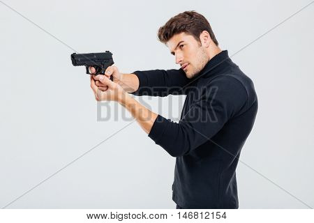 Concentrated young man standing and aiming with gun