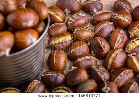 chestnuts in a tin bucket and chestnuts roasted on wood