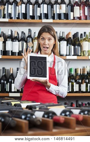 Surprised Saleswoman Showing Blank Digital Tablet In Wine Shop