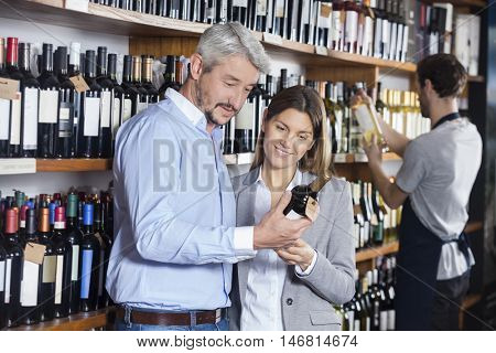 Couple Looking At Wine Bottle In Store