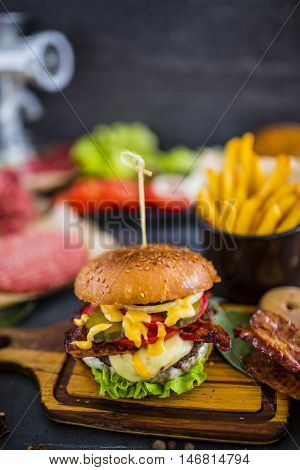 Tasty grilled beef and prawn burger with lettuce and mayonnaise served with golden french fries, chips on olive cutboard on a rustic wooden table