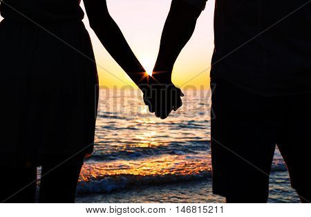 Summer couple holding hands at sunset on beach. Romantic young couple enjoying sun, sunshine, romance and love by the sea. Couple on summer vacation travel holiday