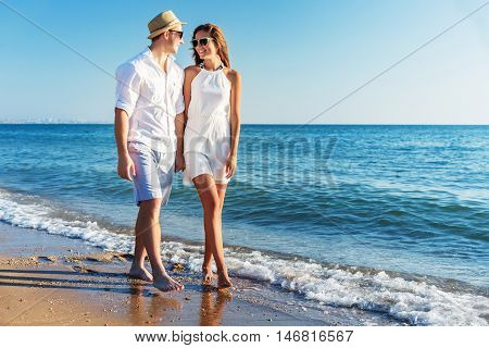 Couple walking on beach. Young happy interracial couple walking on beach smiling holding around each other. Asian woman, Caucasian man