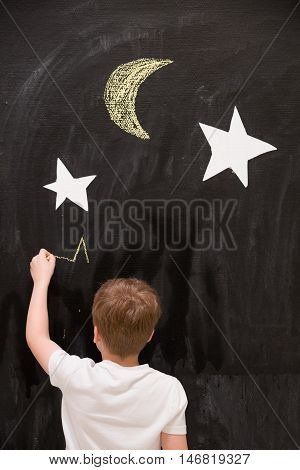 Back view on cute kid boy drawing stars with chalk on a black board with white stars and moon. Child writing on wall in the classroom. Creativity activities for children indoors. Dreaming about space