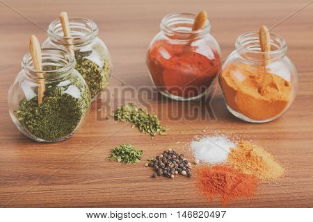 Four glass jar with spices and spices heap on the wooden desk