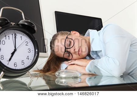 woman sleeping on work in the office desk with clock