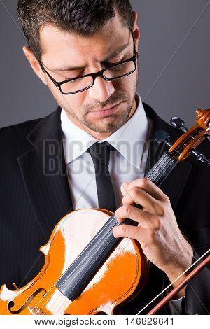 Violinist  playing violin on dark background,