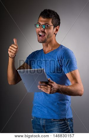 young male executive using digital tablet against gray background