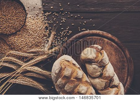 Bread background. Brown and white whole grain loaves composition on rustic wood with wheat ears scattered around. Baking and home bread making concept.
