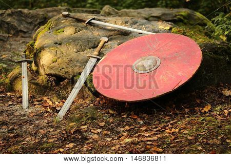 Shield and swords lie on the stone in the forest
