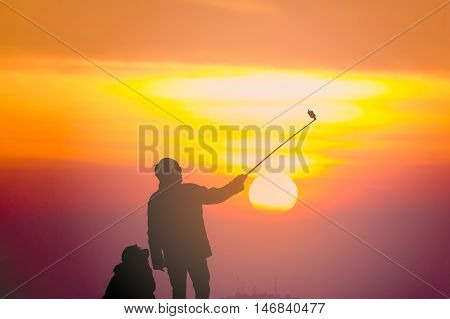 People silhouettes take selfie. At sunset sky orange.