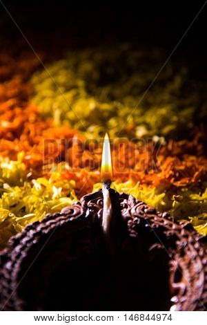 Traditional diya or oil lamp lit on colorful rangoli made up of flower petal, on the festival of lights called diwali or deepawali, selective focus