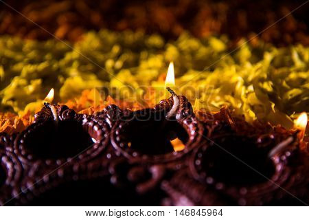 Traditional diya or oil lamp lit on colorful rangoli made up of marigold flower petal, on the festival of lights called diwali or deepawali, selective focus