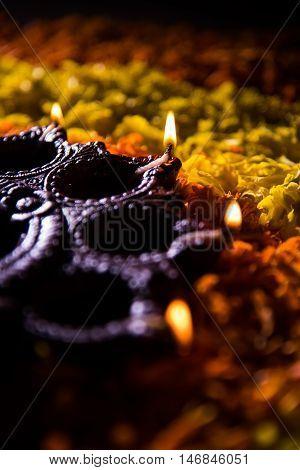 Traditional diya or oil lamp lit on colorful rangoli made up of marigold flower petal, on the festival of lights called diwali or deepawali, selective focus