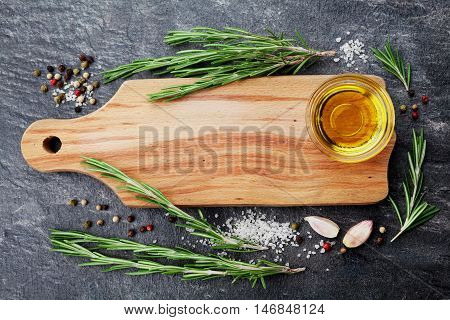 Wooden cutting board, olive oil, rosemary plant, salt, garlic and pepper on black table from above for food cooking background or menu.