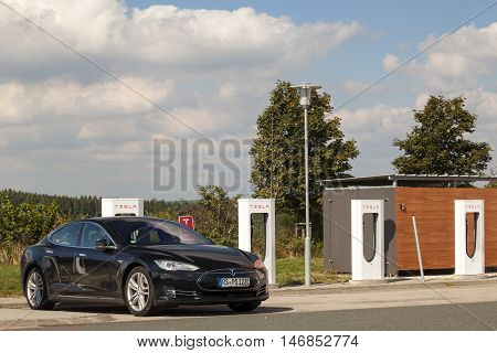 WILNSDORF GERMANY - SEP 1 2016: Tesla Model S electric car being charged at the Tesla Supercharger station