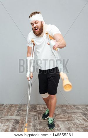 Mad bandaged young man standing and pointing on you with crutches over white background