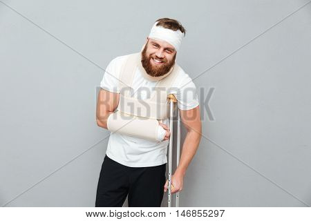 Portrait of smiling bandaged bearded young man standing with crutches over gray background