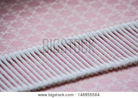 white cotton swabs lying on a pink table with a pattern