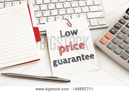 Word text Low price guarantee on white paper card on office table / business concept