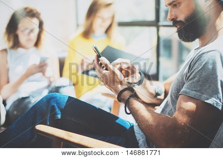 Adult Bearded Hipster Man Using Modern Smartphone.Yound Business People Gathered Together Discussing Creative Idea City Cafe.Coworkers Meeting Communication Discussion Working Office Startup Concept